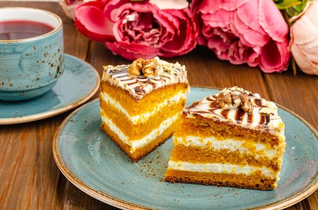 Dwa kawałki ciasta marchewkowego na niebieskim talerzu filiżanka herbaty na drewnianym stole