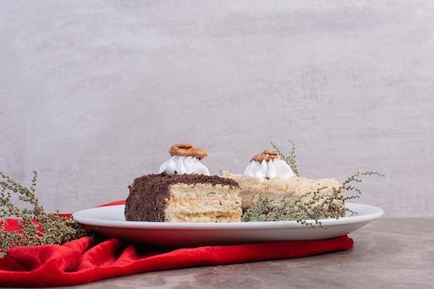 Dwa kawałki ciasta na białym talerzu z czerwonym obrusem.