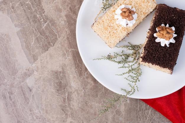 Dwa kawałki ciasta na białym talerzu.