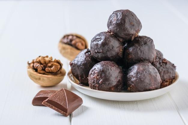 Dwa kawałki czekolady, dwa orzechy włoskie i domowe cukierki z suszonych owoców na białym drewnianym stole. pyszne, świeże, domowe cukierki.