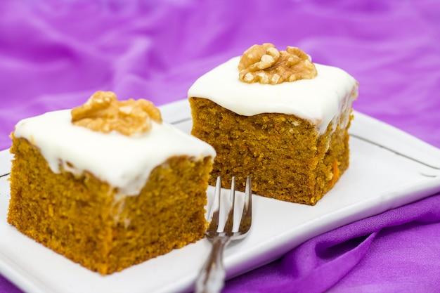 Dwa kawałki domowego ciasta marchewkowego z pomarańczą, skórką, orzechami i lukrem na liliowym tle. selektywne ustawianie ostrości