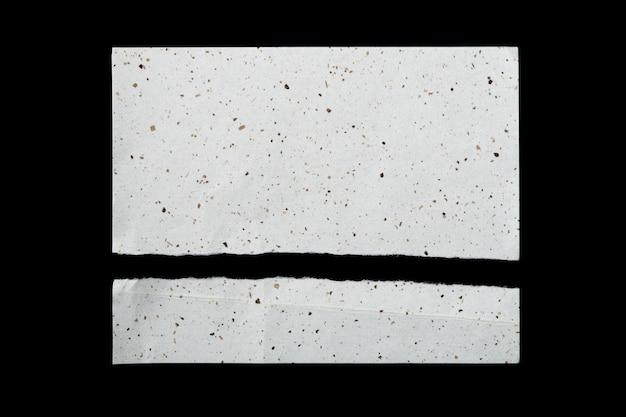 Dwa kawałki poszarpanego papieru czerpanego na czarnym tle