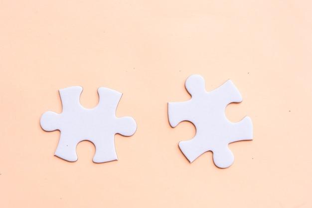 Dwa kawałki puzzli na różowym tle