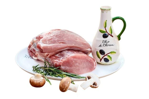 Dwa kawałki surowej polędwiczki wieprzowej i oliwy z oliwek w butelce, gałązka rozmarynu na białym talerzu z grzybami