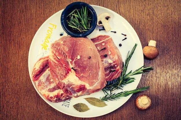 Dwa kawałki surowej polędwiczki wieprzowej, rozmaryn na białym talerzu z pieczarkami, widok z góry
