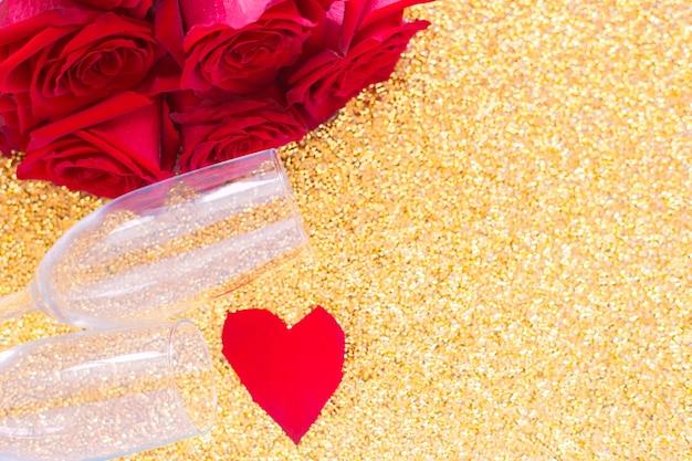 Dwa kieliszki do szampana, czerwony bukiet róż i serce z płatków leżą z boku na jasnym złotym...