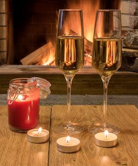 Dwa kieliszki do szampana i świece przed przytulnym kominkiem.