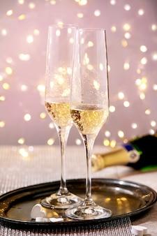 Dwa kieliszki do szampana na tacy stojącej na srebrnym musującym stole, białe serca, światła bokeh. świąteczne nakrycie stołu.