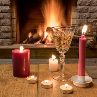 Dwa kieliszki do szampana, świece przed przytulnym ogniem.