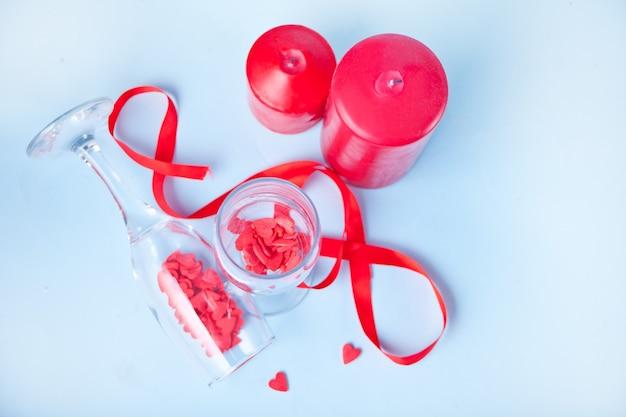 Dwa kieliszki do szampana z czerwonymi cukierkami w kształcie serca i czerwonymi świecami na tle. koncepcja walentynki.