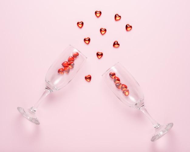 Dwa kieliszki do szampana z czerwonymi serduszkami na różowej powierzchni.