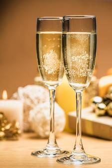 Dwa kieliszki do szampana z dekoracjami świątecznymi i gałęzią jodły na białym tle