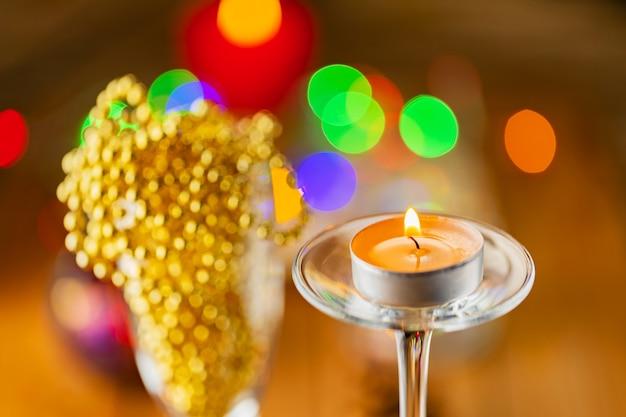Dwa kieliszki do szampana z koralikami świątecznymi. ozdoby świąteczne w stylu rustykalnym na jasnym tle ze światłami. szyszki i płonące świeczki na tle bokeh