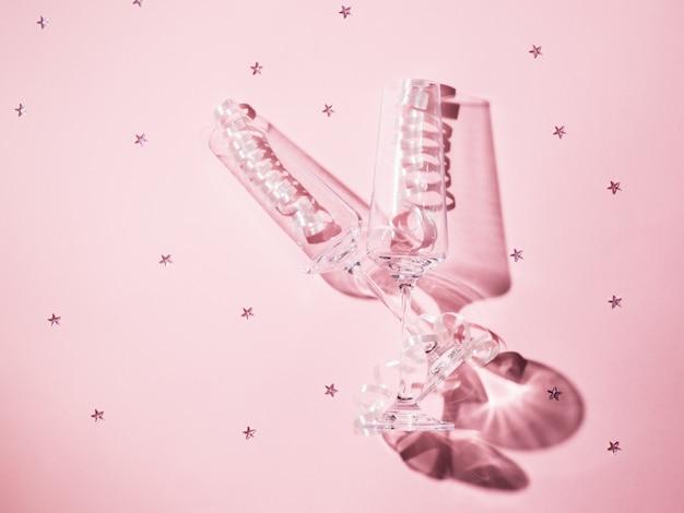 Dwa kieliszki do szampana z serpentynami na różowym tle z rozsypanymi cekinami w ostrym świetle. świąteczny tło z kieliszkami do szampana.