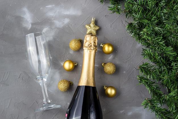 Dwa kieliszki do szampana ze złotymi kulkami i złotą butelką szampana, zielone jodły na szarym tle, kopia przestrzeń. świąteczna kompozycja płasko świecka na boże narodzenie lub nowy rok.
