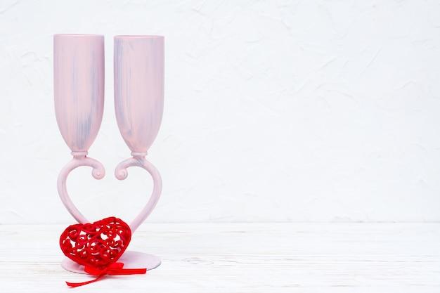 Dwa kieliszki do wina tworzą serce w kształcie serca i czerwone serce w kształcie serca na białym stole