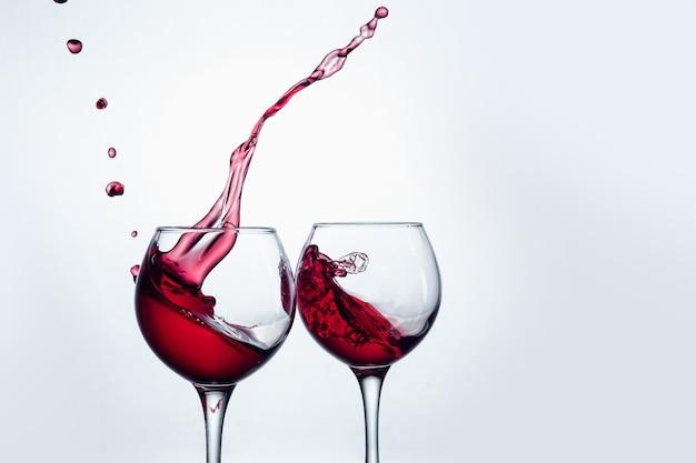Dwa kieliszki do wina w geście opiekania z dużym rozpryskiwaniem się w studio.
