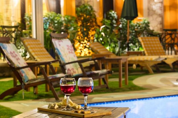 Dwa kieliszki wina w pobliżu basenu w nocy