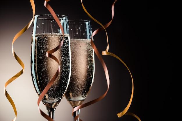 Dwa kieliszki z szampanem musującym i ozdobnymi wstążkami. koncepcja wakacji