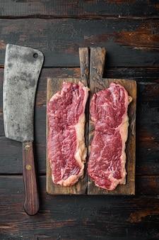 Dwa klasyczne steki ze świeżej wołowiny na starym ciemnym drewnianym stole