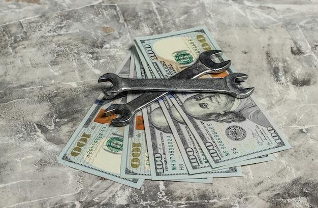 Dwa klucze i dolary na szarym tle betonu. narzędzie pracy