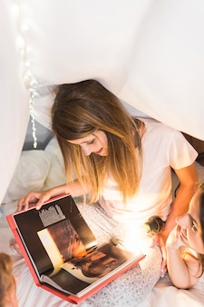 Dwa kobiet czytelniczy magazyn z iluminującą latarką na łóżku