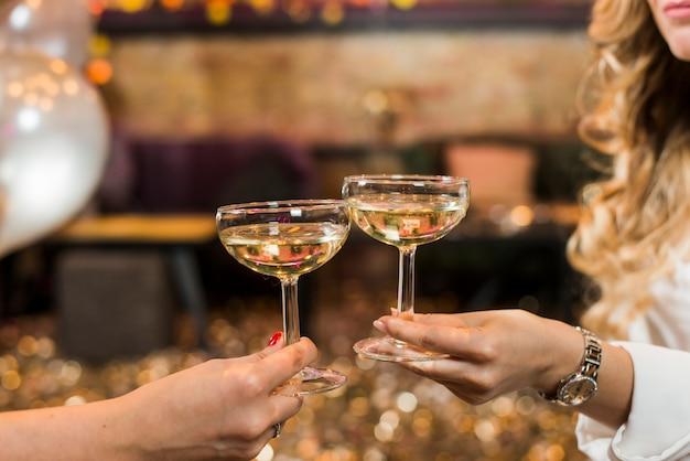 Dwa kobiet ręka wznosi toast whisky przy noc klubem