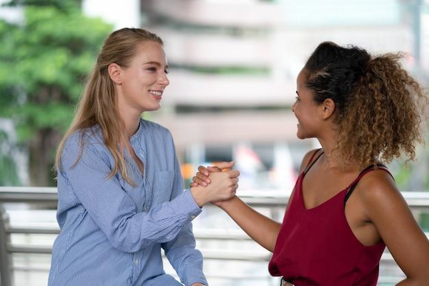 Dwa kobieta przyjaciela trzyma ręki powitanie na miasto ulicie