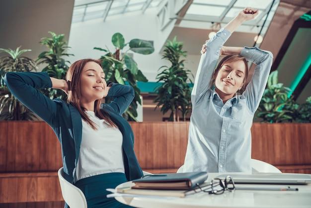 Dwa kobiety ćwiczy rozciąganie przy biurkiem w biurze.