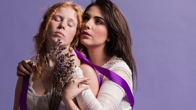 Dwa kobiety pozuje z lawendą i faborkiem podczas gdy ściskający z kopii przestrzenią
