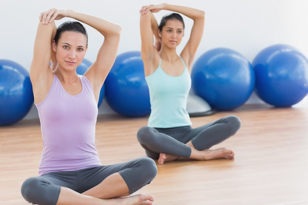 Dwa kobiety rozciąga ręki w sprawności fizycznej studiu