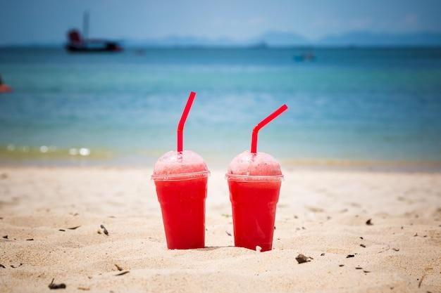 Dwa koktajle arbuzowe w jednorazowych plastikowych kubkach z rurkami orzeźwiający tropikalny styl życia na plaży