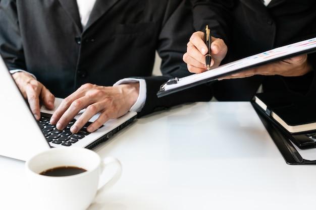 Dwa kolegi dyskutuje dane z komputerowym laptopem na biurko stole w biurze. zamyka w górę biznes drużyny analizy i strategii pojęcia.