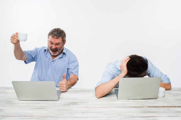 Dwa kolegi pracuje wpólnie przy biurem na białym tle