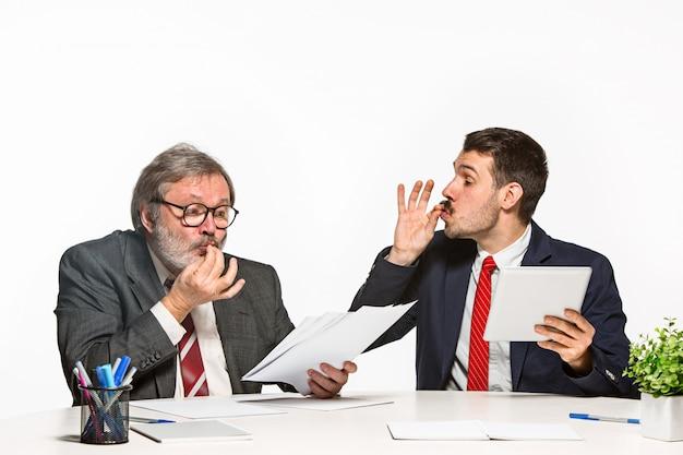 Dwa kolegi pracuje wpólnie przy biurem na białym tle.