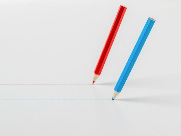 Dwa kolorowe kredki rysujące proste linie na białym tle. pojęcie współpracy.