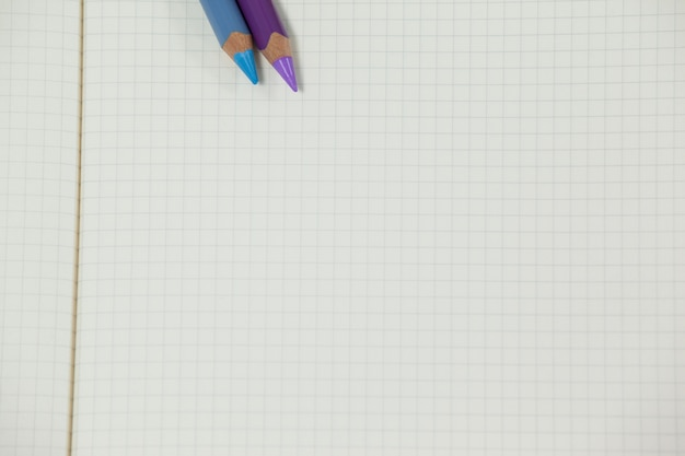 Dwa kolorowe kredki trzymane w notesie