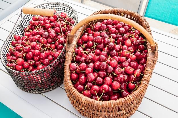 Dwa kosze wypełnione pięknymi czerwonymi wiśniami na ogrodowym stole