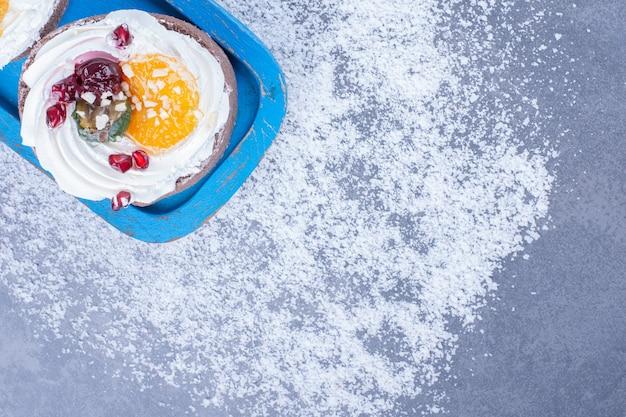 Dwa kremowe ciastka z cukrem pudrem na niebieskiej desce