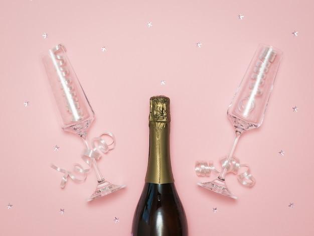 Dwa kryształowe kieliszki do szampana na świątecznym różowym tle z butelką szampana. świąteczny tło z kieliszkami do szampana.