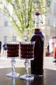 Dwa kryształowe kieliszki i butelka z likierem wiśniowym