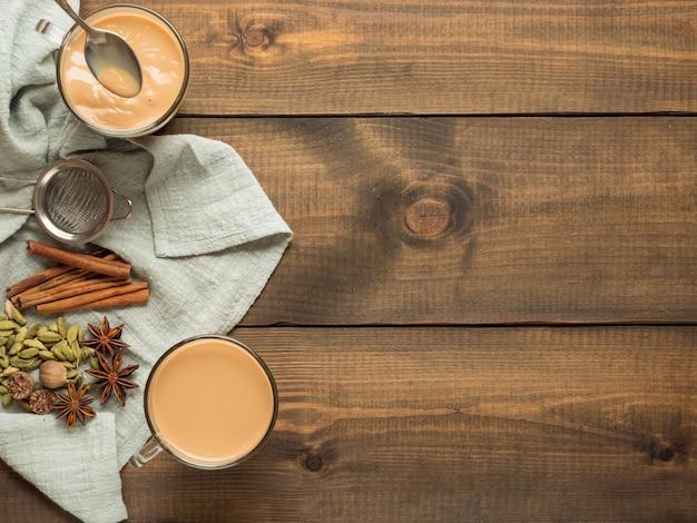 Dwa kubki z herbatą masala stoją na drewnianym stole z przyprawami. widok z góry.