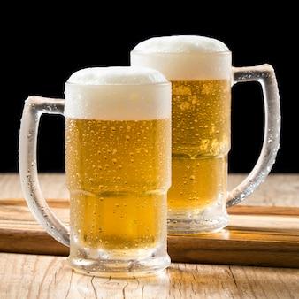 Dwa kufle piwa z beczki na drewnianym stole