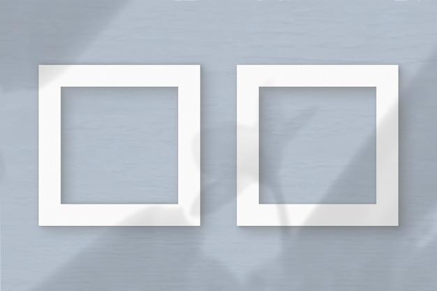 Dwa kwadratowe ramki arkusza białego papieru z teksturą na tle szarej ściany. makieta z nakładką cieni roślinnych. naturalne światło rzuca cienie z liści egzotycznej rośliny. płaski układanie, widok z góry