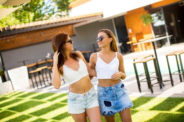 Dwa ładnej młodej kobiety pozuje w podwórzu przy gorącym letnim dniem