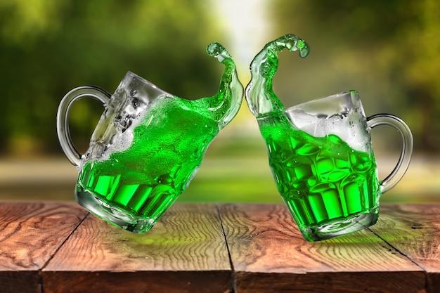 Dwa latające kufle do piwa z zielonym świeżym alkoholowym napojem na drewnianym stole przeciwko naturalnej, kopiowanej przestrzeni. koncepcja happy st patrick's day.