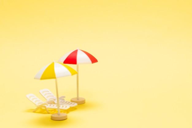 Dwa leżaki i czerwony parasol na żółtym tle. skopiuj miejsce.