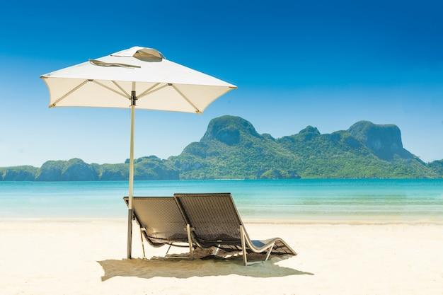 Dwa leżaki pod niebieskim parasolem na białej, piaszczystej plaży w ośrodku