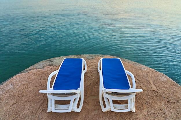 Dwa leżaki stoją nad pięknym morzem