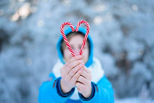 Dwa lizaki w kształcie czerwono-białego serca na rozmytym tle świateł bokeh. miłość w walentynki. świąteczne słodycze